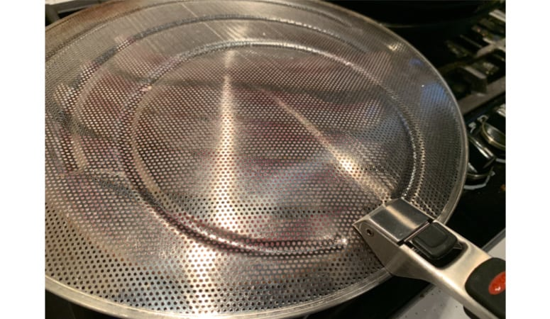 A splatter shield over a frying pan.