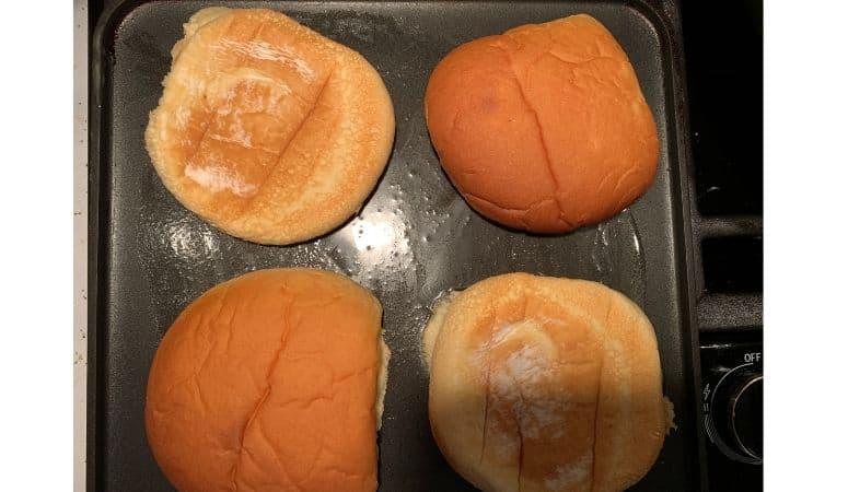 hamburger buns toasting on a griddle